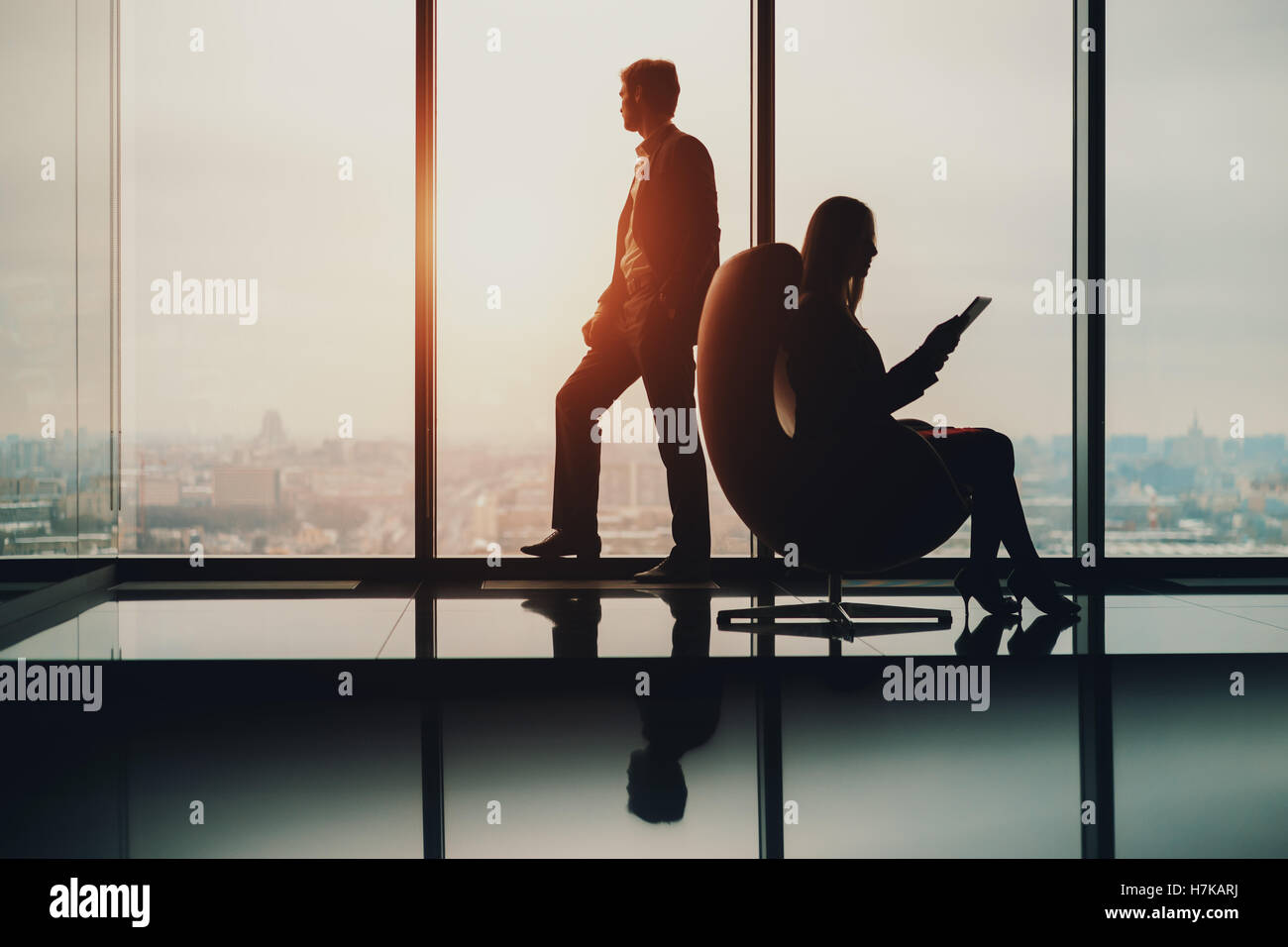 Silhouette of businessman standing next to big window, looking at blurred cityscape outside, his female colleague - Stock Image
