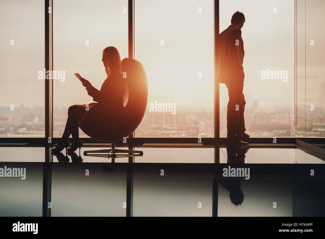 Silhouette of businessman standing next to window, looking at blurred city outside on sunset, his female colleague - Stock Image