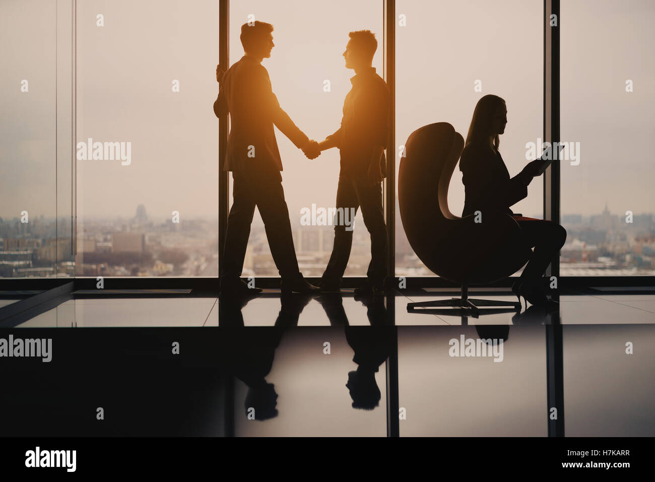 Silhouettes of two young businessmen in luxury office interior completing deal with handshake, female secretary - Stock Image
