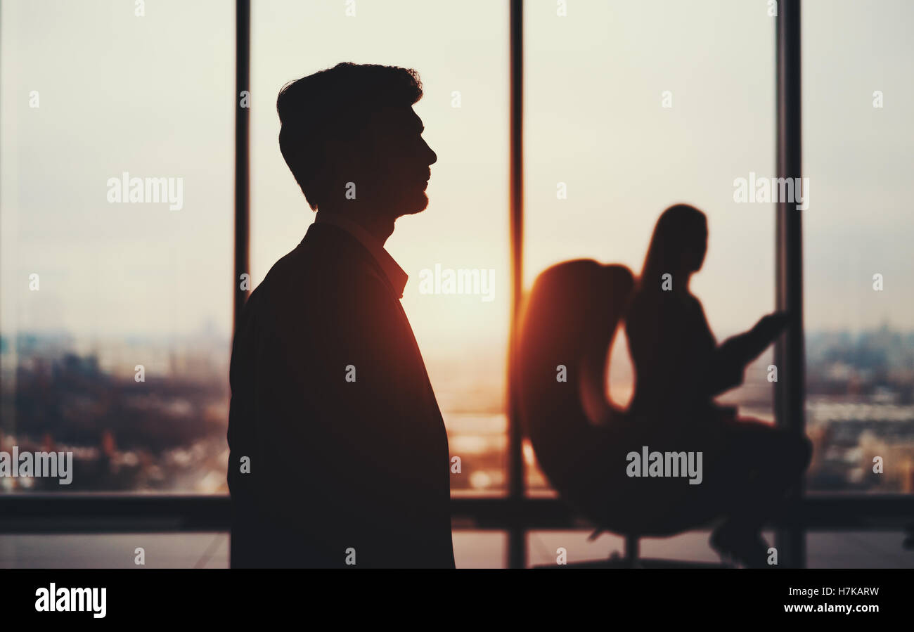 Silhouette of young elegant bearded businessman in formal suit standing in front of window and his female colleague - Stock Image