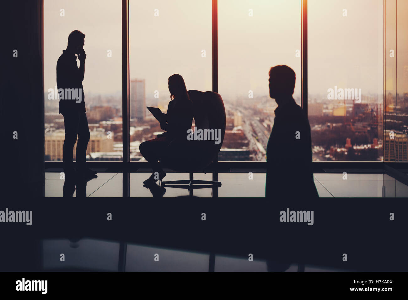Silhouettes of business people: businessman with businesswoman waiting for their third colleague which is already - Stock Image