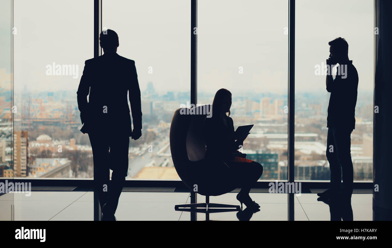 Silhouettes of business people: businessman with businesswoman waiting for their third colleague which is coming - Stock Image