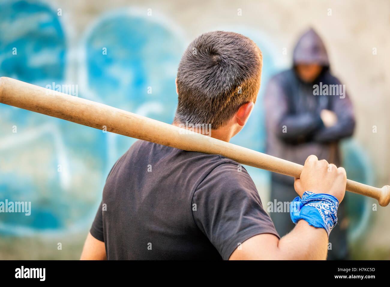 Aggressive teenager with a baseball bat against man at outdoor - Stock Image