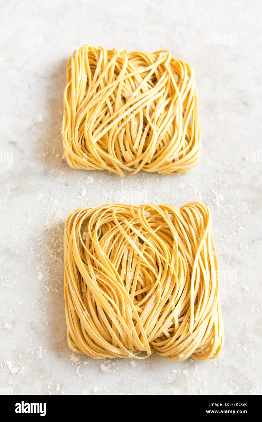 Raw uncooked homemade italian pasta tagliatelle (chinese egg noodles) over rustic white stone background with copy - Stock Image