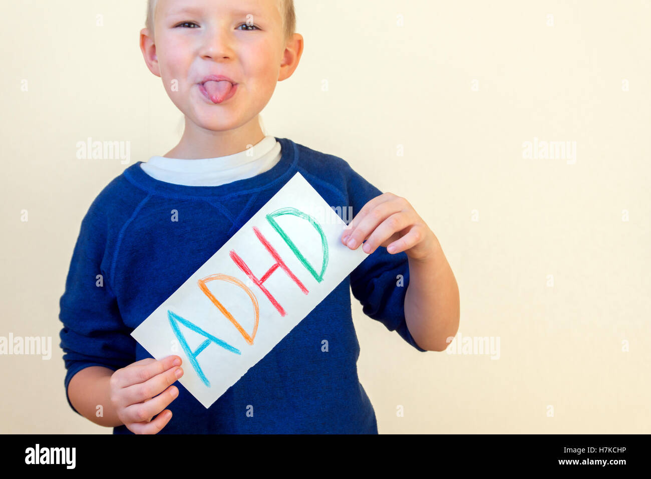Young boy hold ADHD text written on sheet of paper and show his tongue. ADHD is Attention deficit hyperactivity - Stock Image