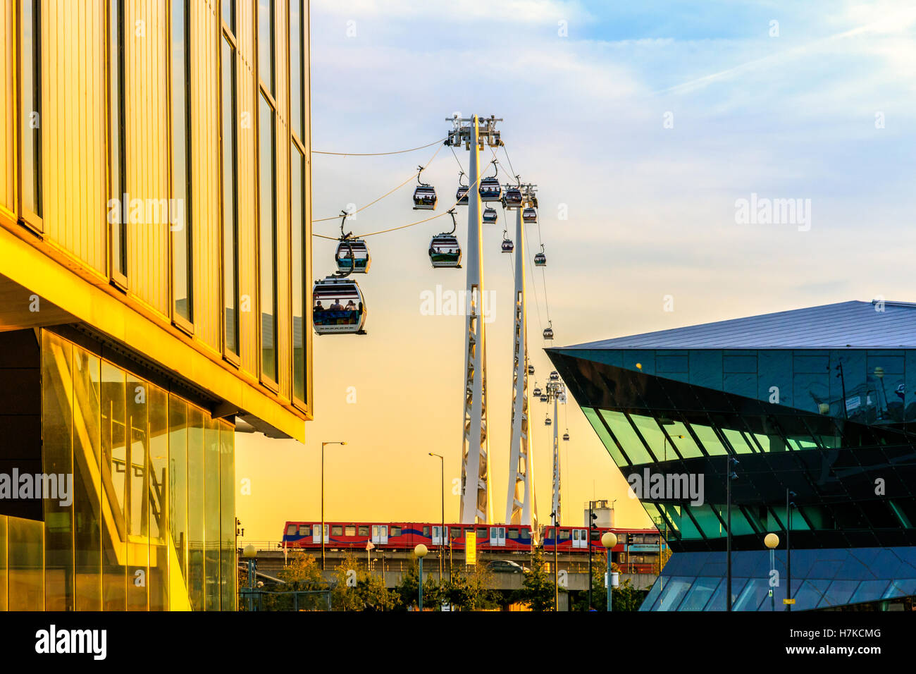 Royal Victoria Dock in London at sunset with Thames cable car and docklands light railway - Stock Image