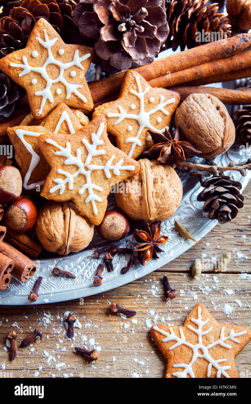 Christmas decor with homemade gingerbread cookies stars, cones, nuts and Christmas spices over rustic wooden background - Stock Image