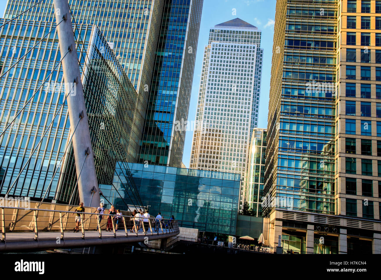 London, UK - August 29, 2016 - People walking on the South Quay footbridge in Canary Wharf with One Canada Square - Stock Image