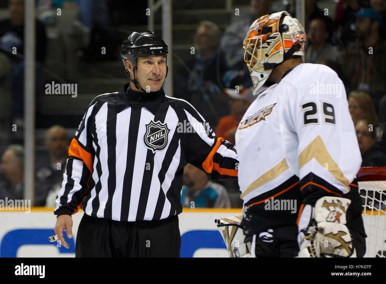 April 2, 2011; San Jose, CA, USA;  NHL referee Stephen Walkom (24) talks to Anaheim Ducks goalie Ray Emery (29) - Stock Image