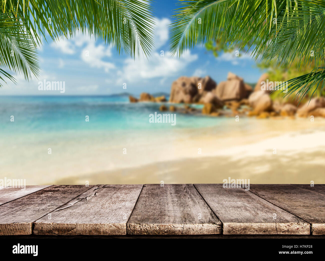 Empty wooden planks with tropical beach on background. Ideal for product placement - Stock Image