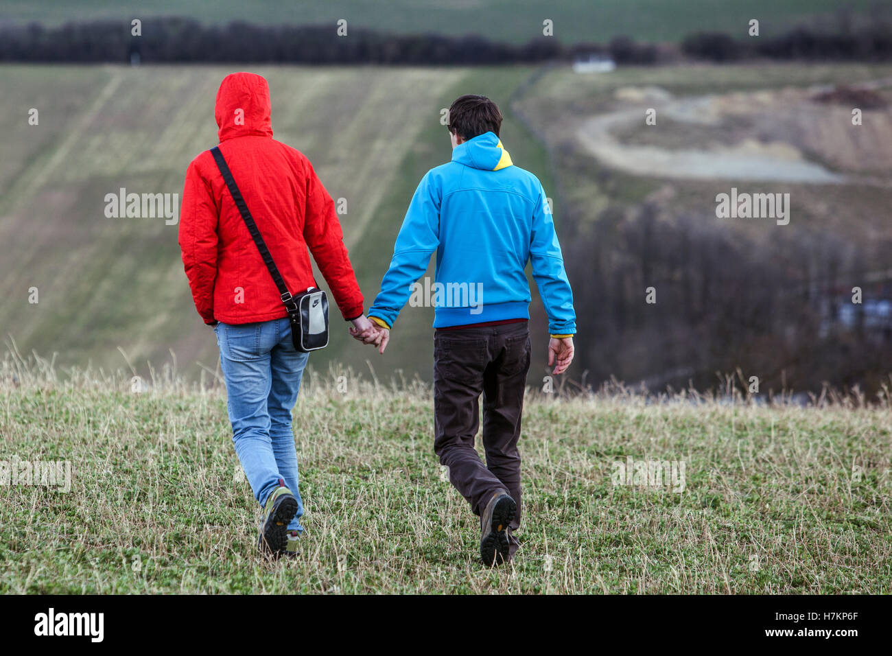 Young people passing through the countryside, a couple holding hands, Czech Republic - Stock Image