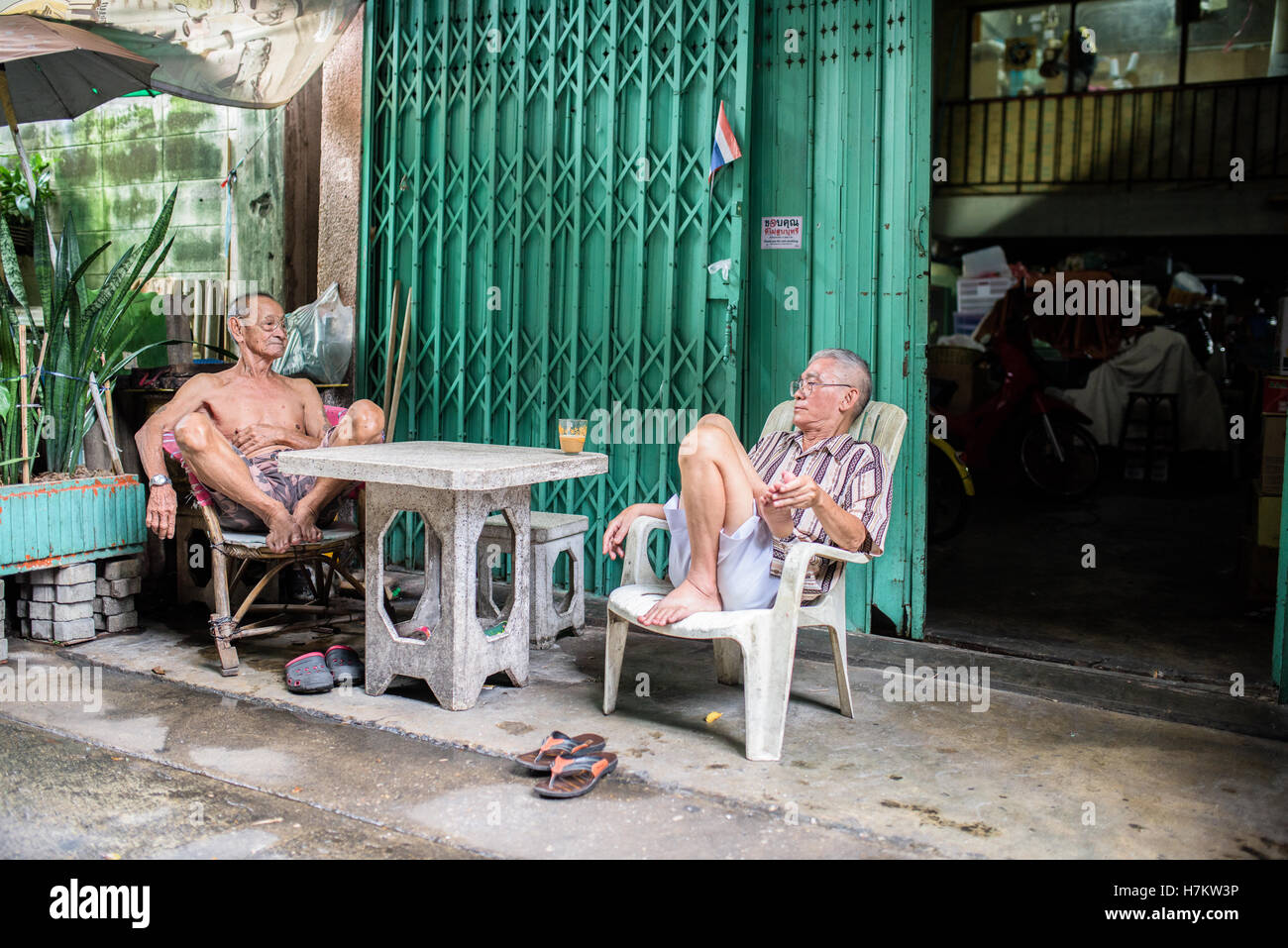 Two older men sitting in front of the house in Bangkok - Stock Image