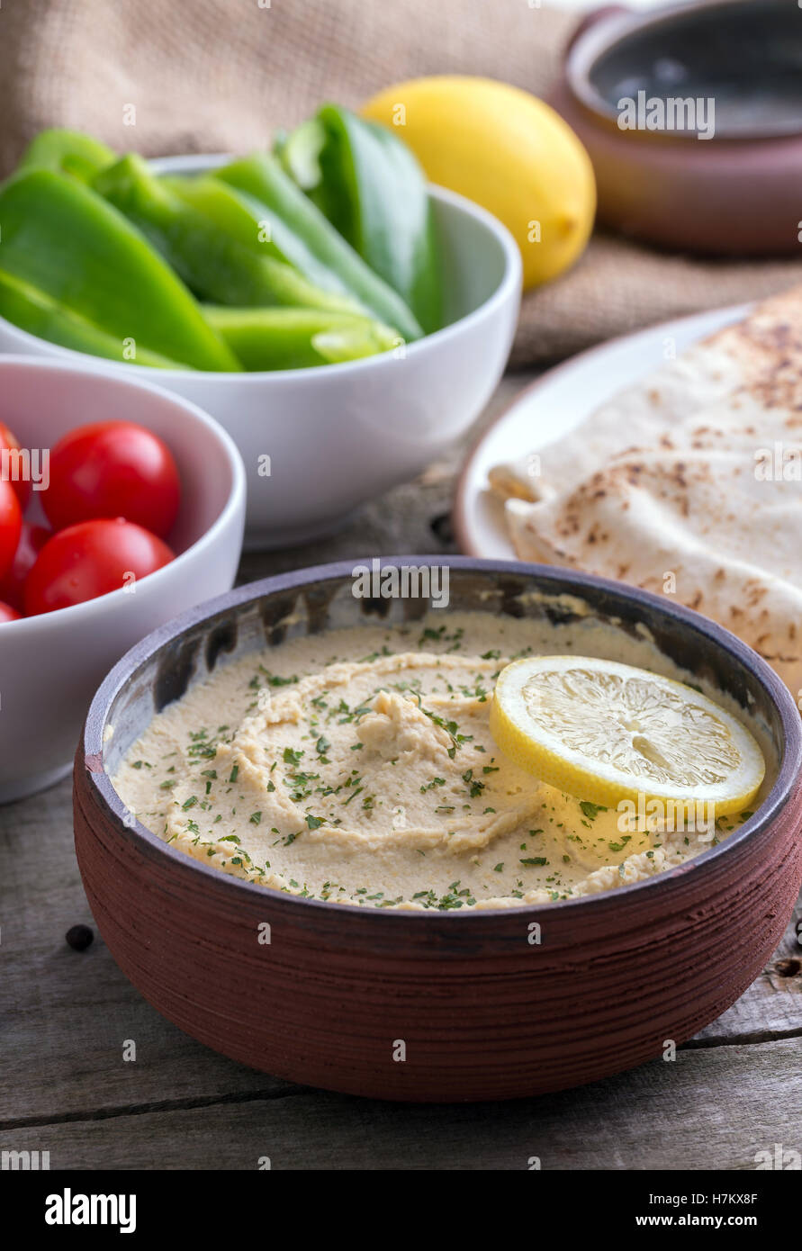 Humus in homemade bowl chapati and vegetable. - Stock Image