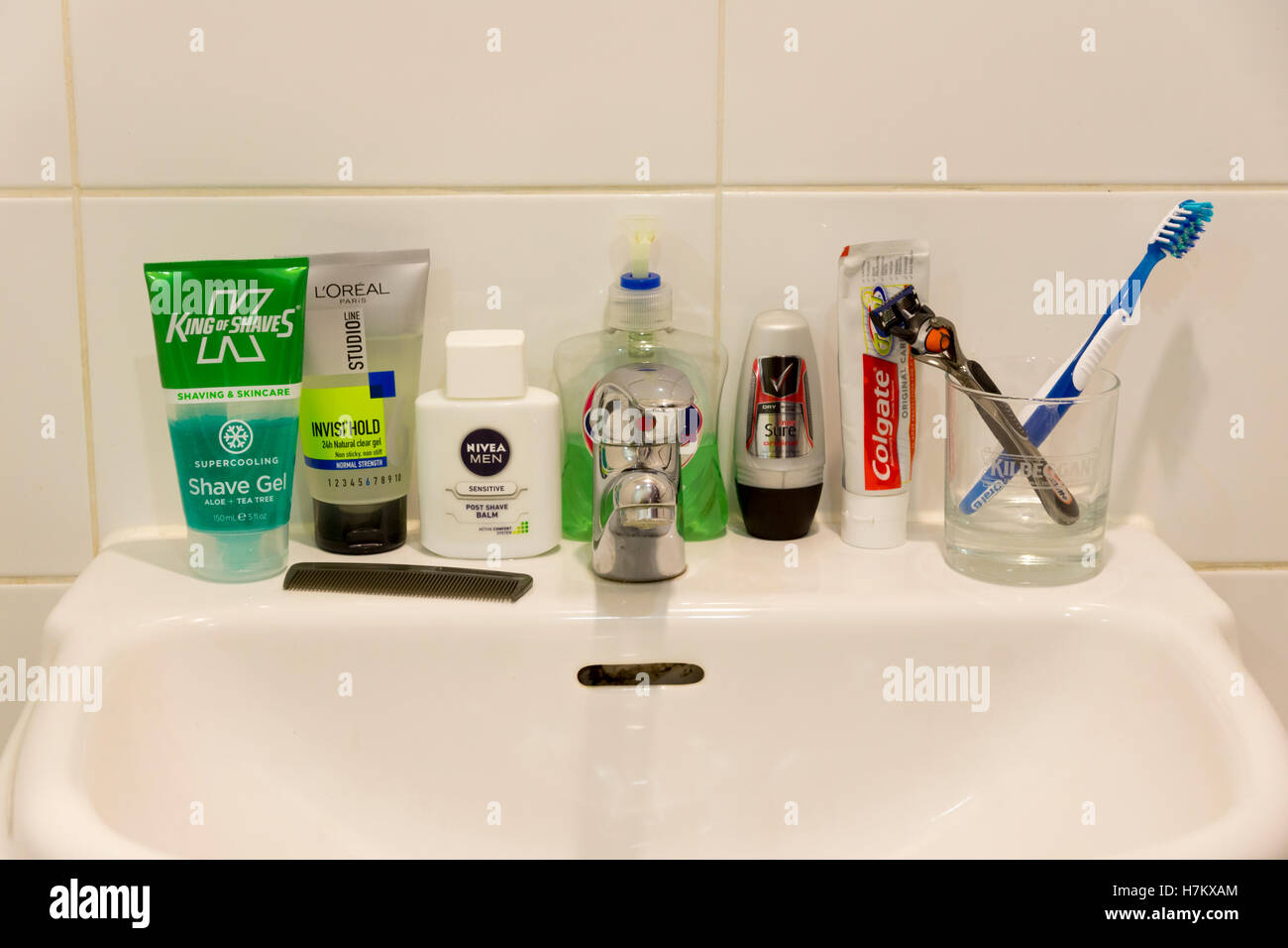 A selection of male toiletries on a bathroom sink - Stock Image