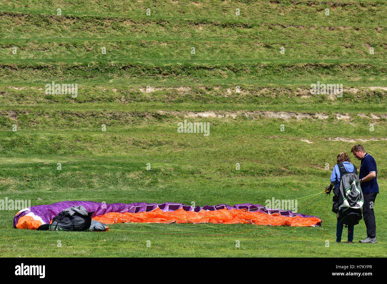 Learning paragliding with a colourful deflated parachute resting on the grass. - Stock Image