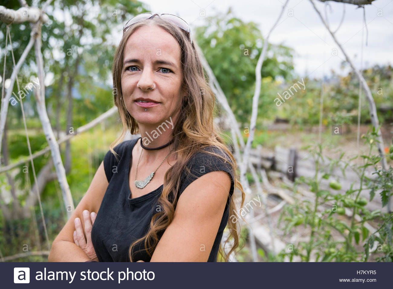 Portrait confident woman with arms crossed in vegetable garden - Stock Image