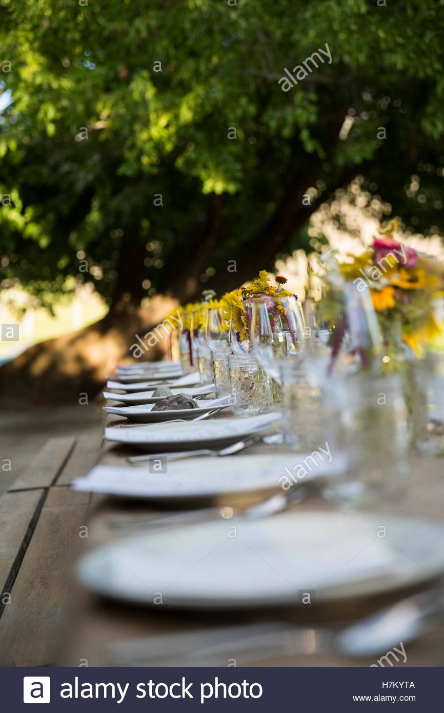 Placesettings in a row for harvest dinner on long patio table - Stock Image