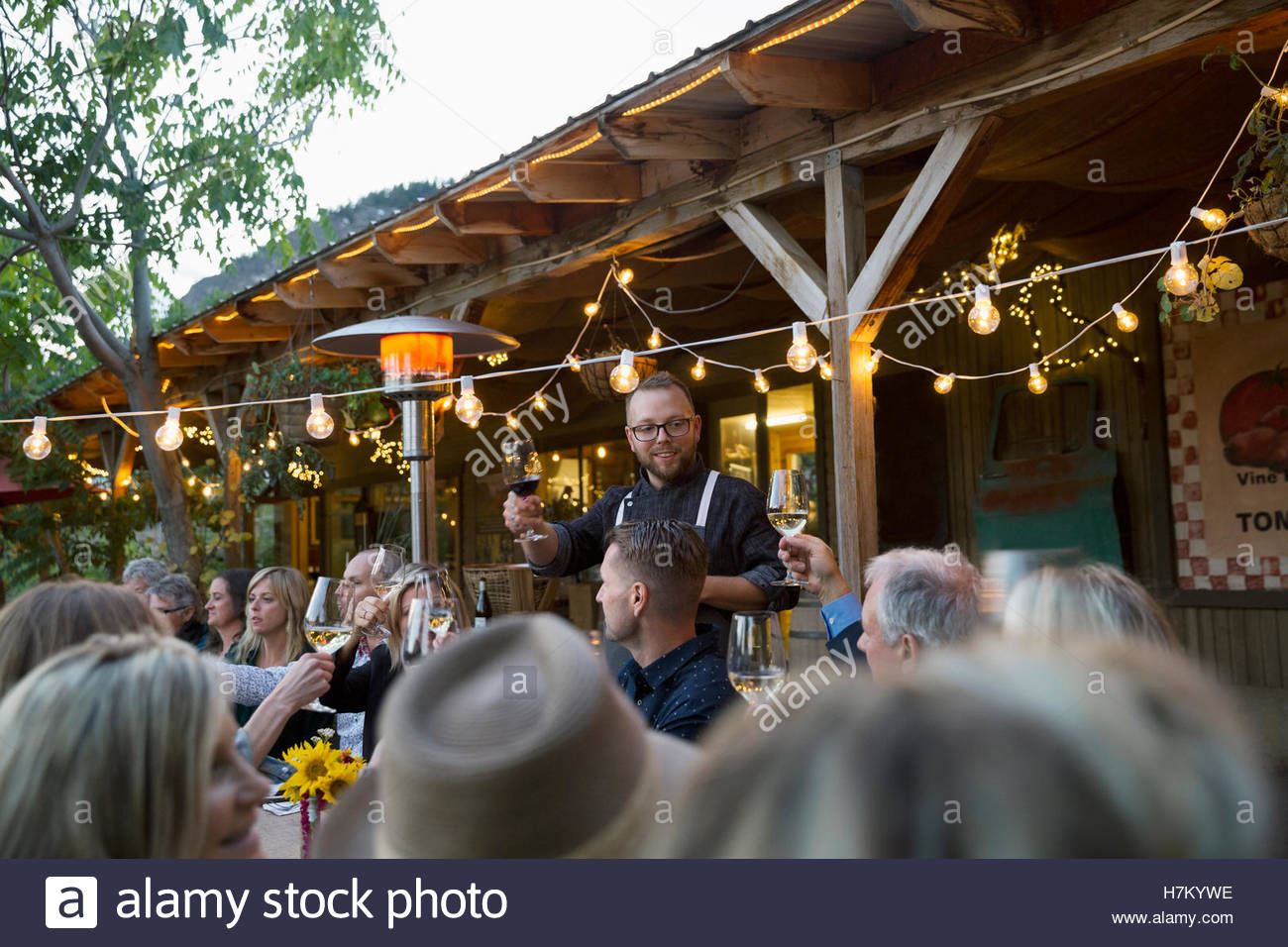 Man leading toast at outdoor dinner party under string lights Stock Photo