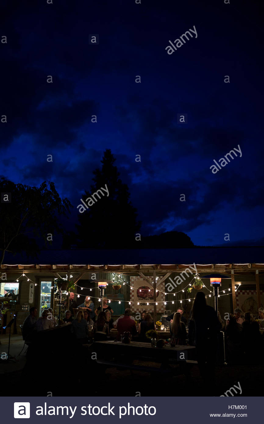 String lights illuminating outdoor patio dinner party - Stock Image