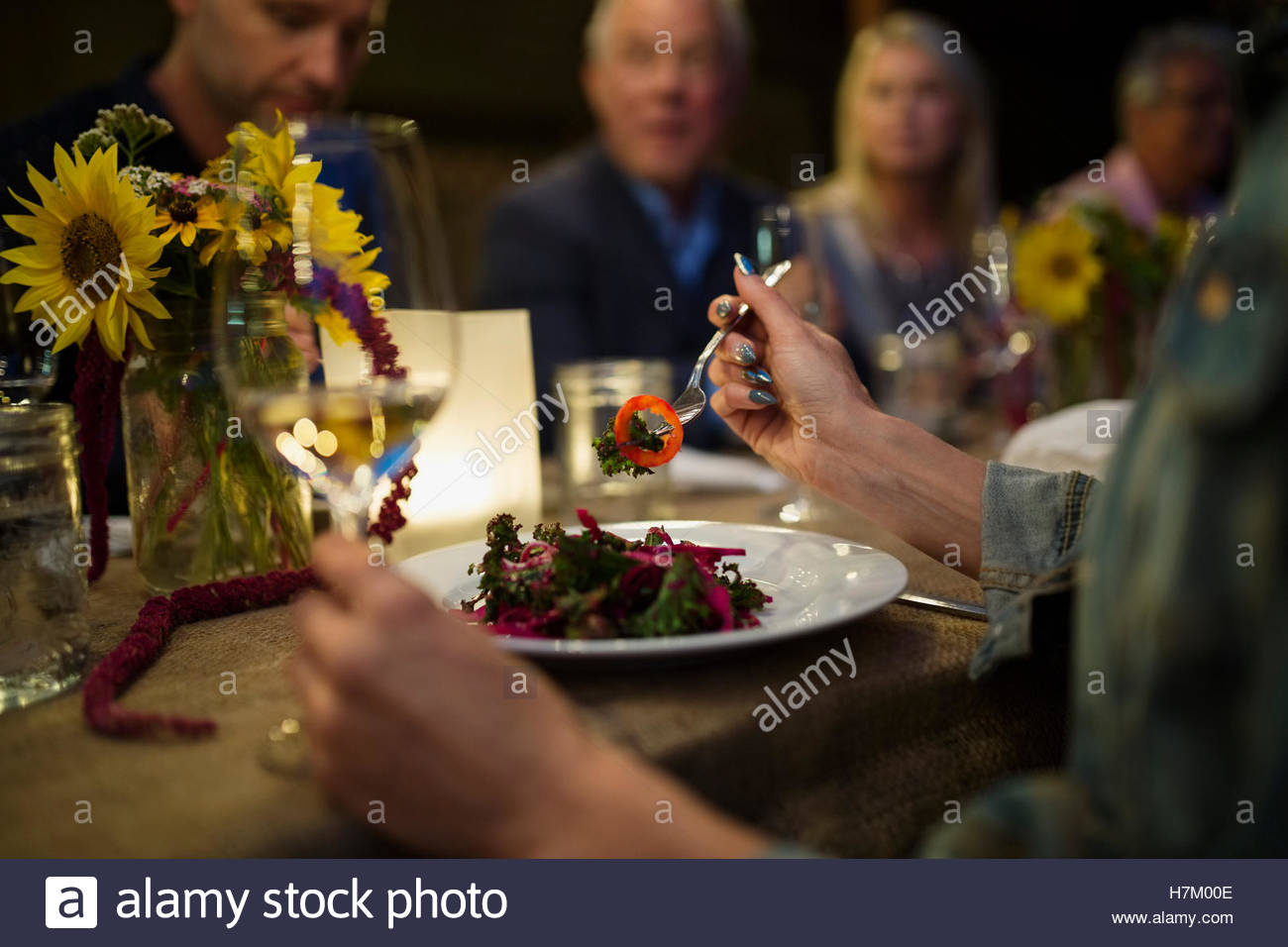 Woman eating at candlelight outdoor dinner party - Stock Image