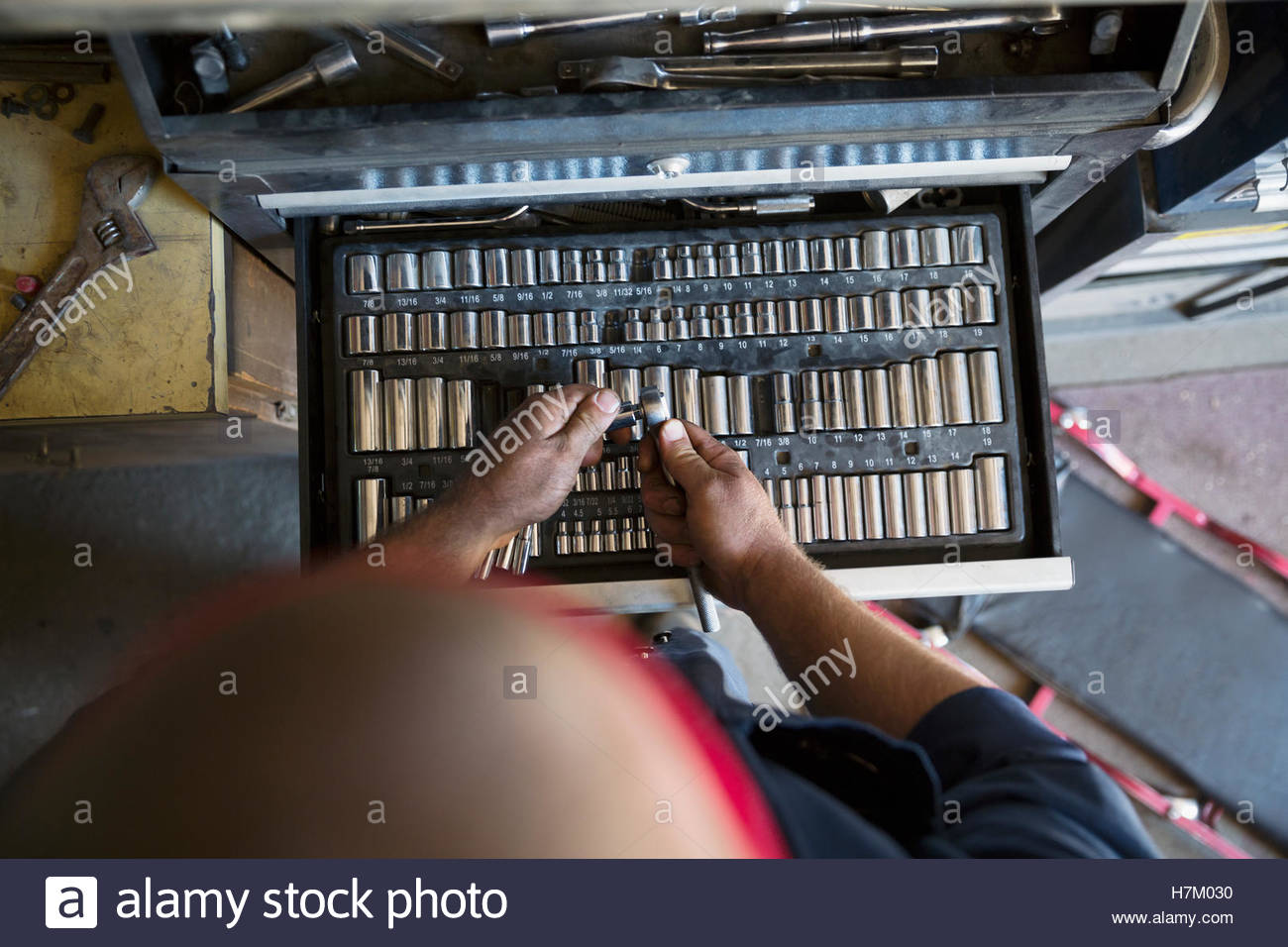 Overhead view of male mechanic choosing drill bit from tool box in workshop - Stock Image