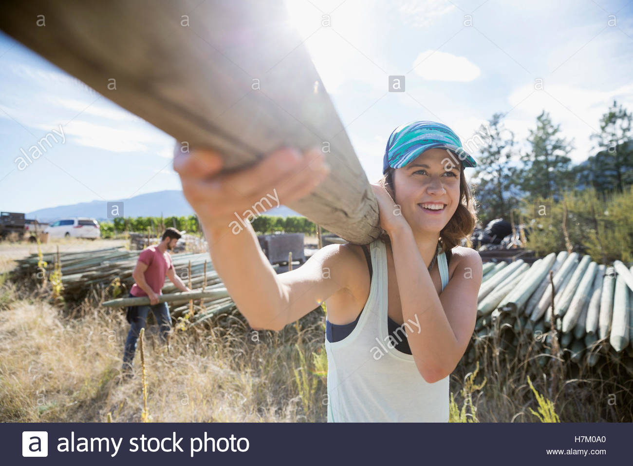 Smiling female farmer carrying wood fence post on sunny farm - Stock Image