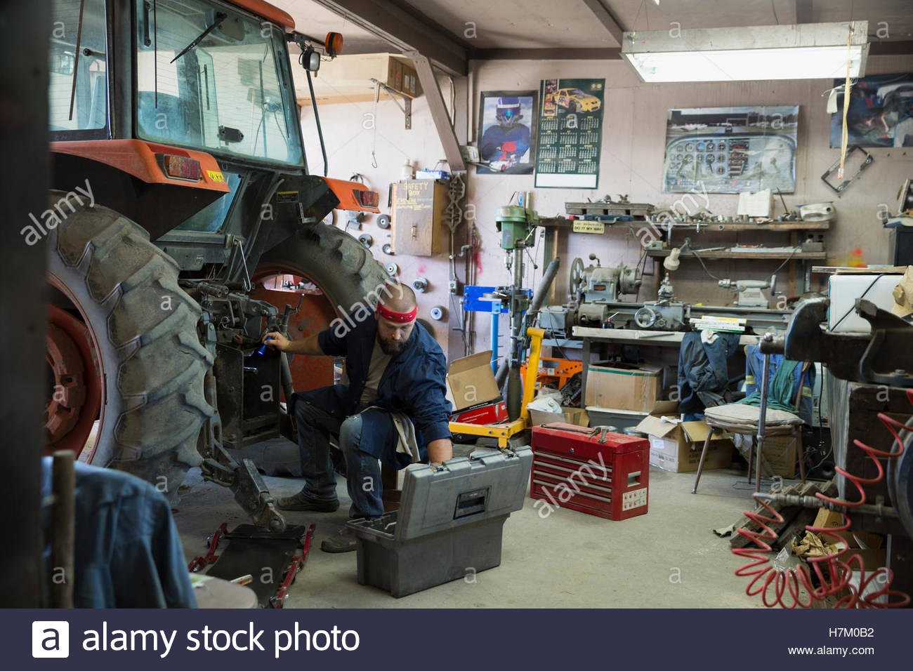Mechanic with tool box working on tractor in workshop - Stock Image