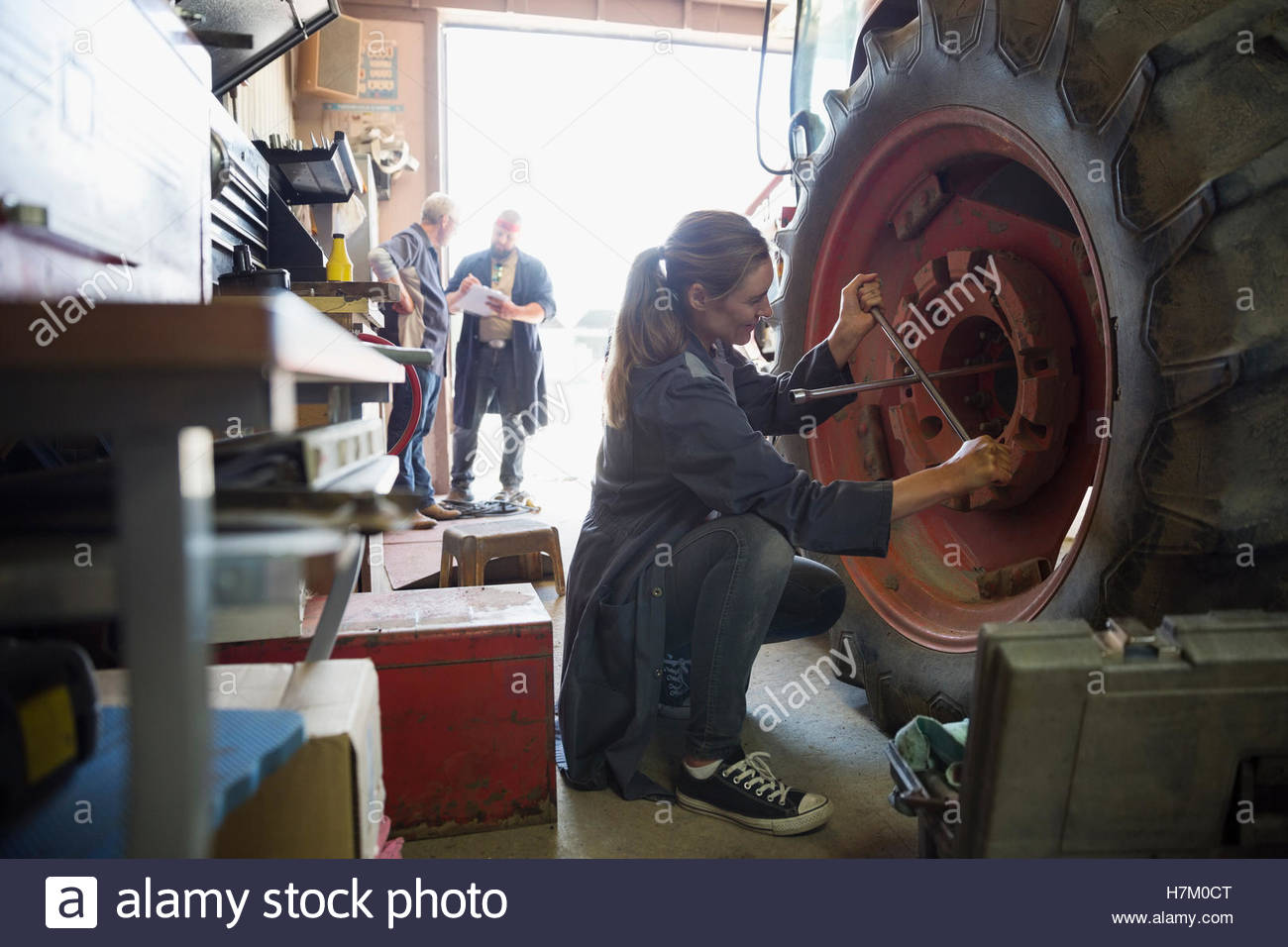 Female mechanic using lug wrench on tractor tire in workshop - Stock Image