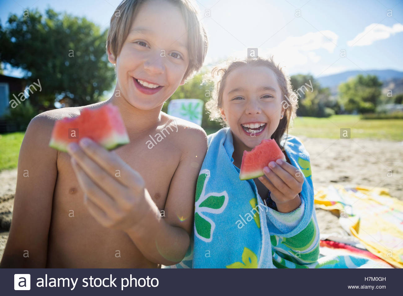 Portrait smiling brother and sister eating watermelon on sunny summer beach - Stock Image