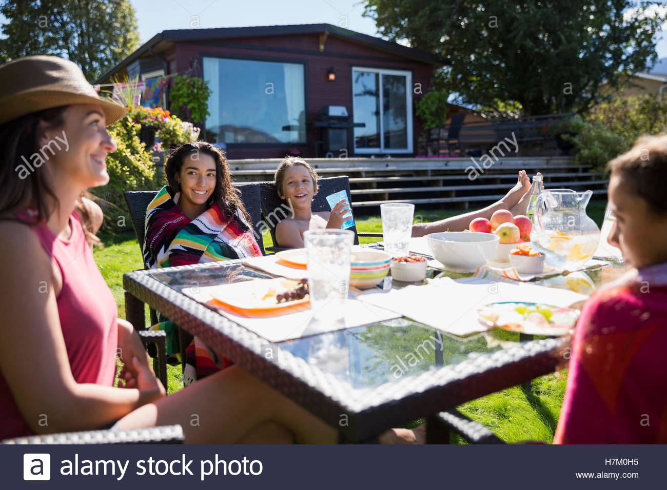 Family eating at sunny summer patio table - Stock Image