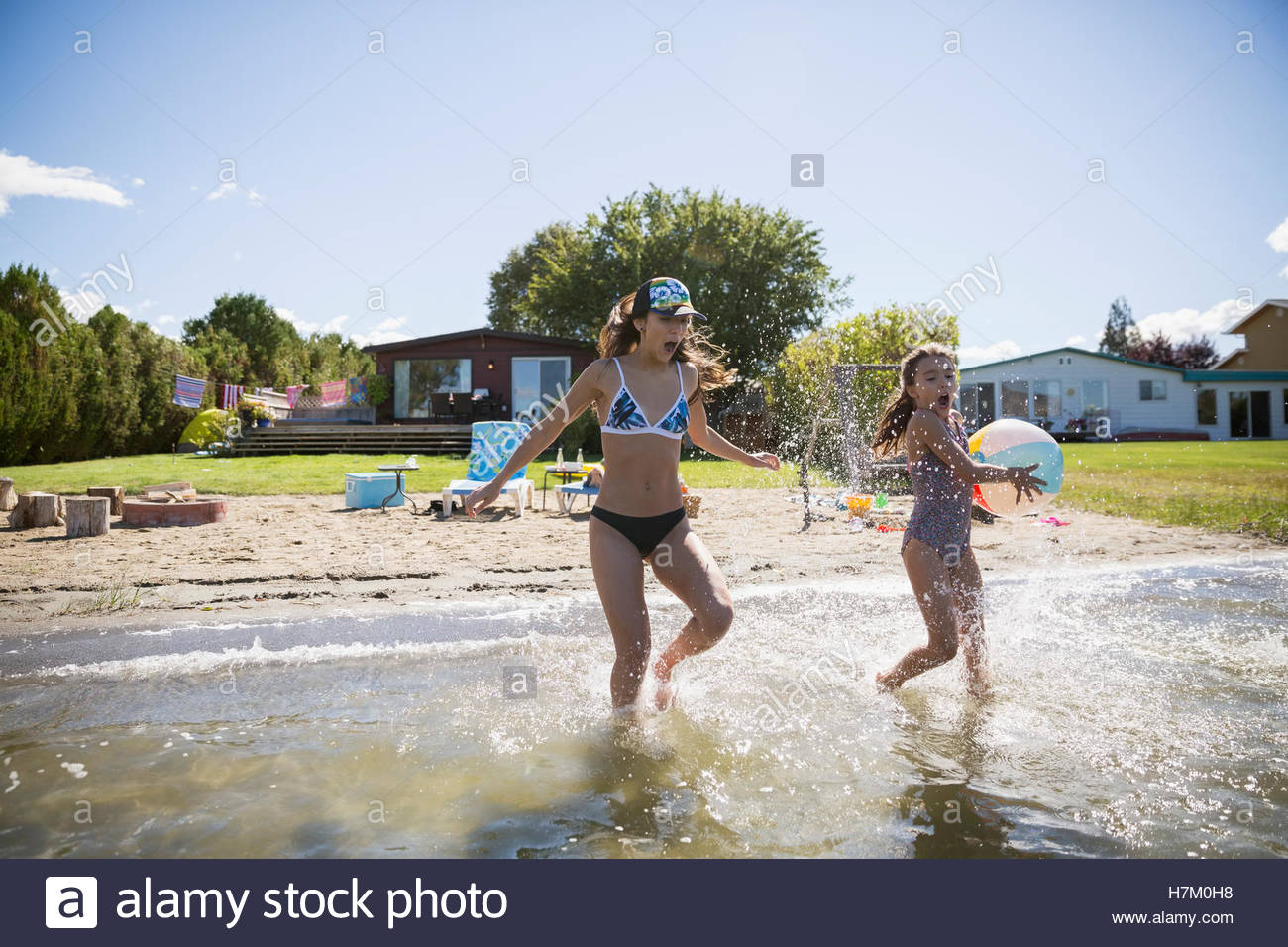 Sisters running and splashing in sunny summer lake - Stock Image