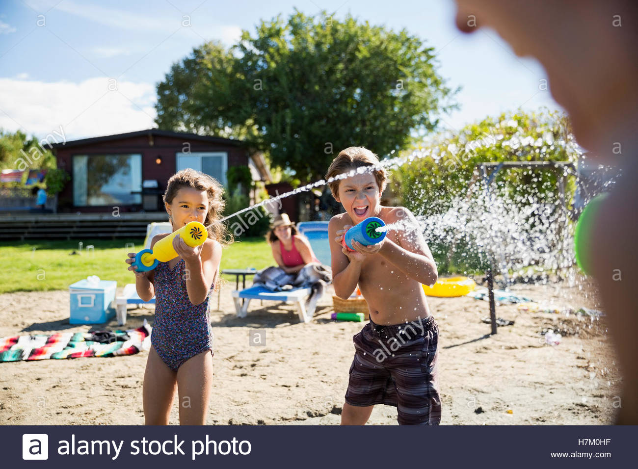 Brother and sister playing with squirt guns at sunny summer beach - Stock Image