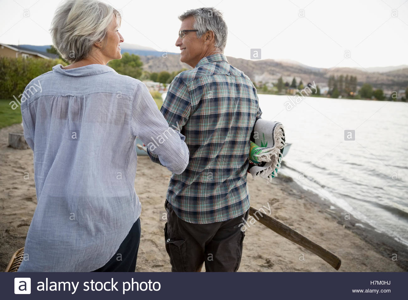 Retired couple walking arm in arm on lake beach - Stock Image
