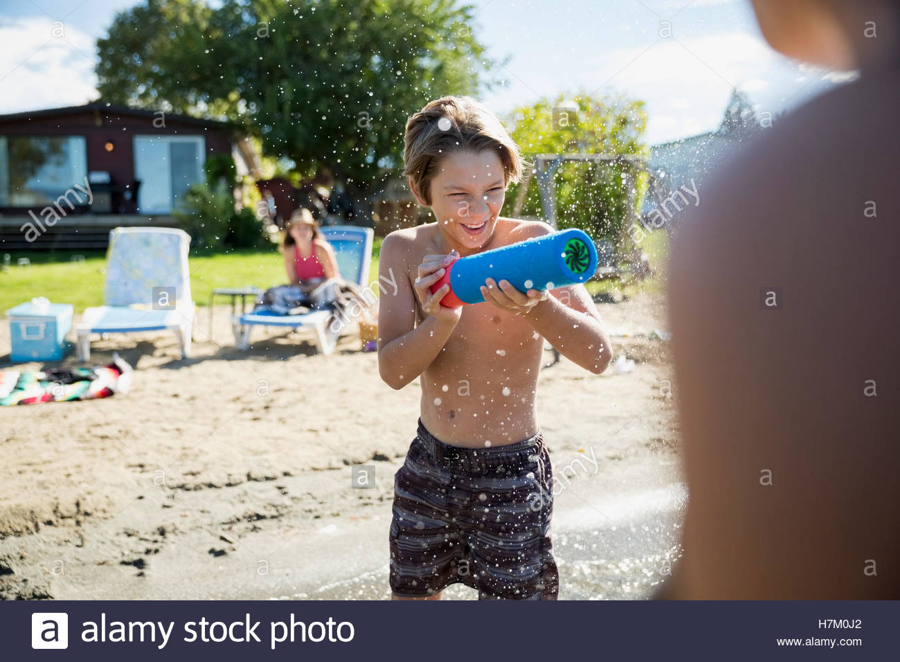Boy playing with squirt gun at sunny summer beach - Stock Image