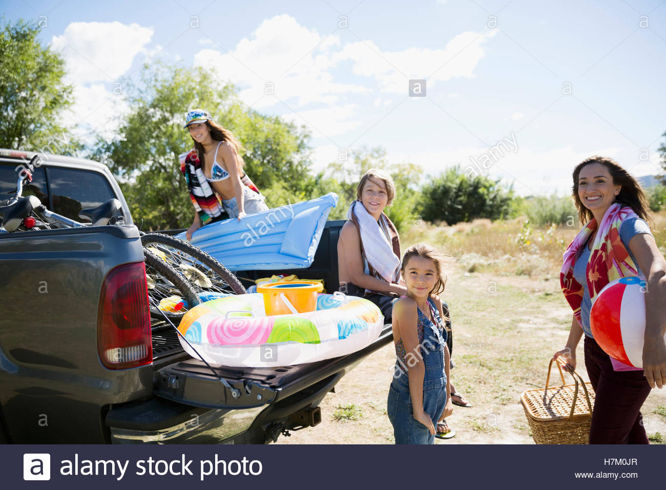 Portrait smiling family with beach equipment at sunny truck bed - Stock Image