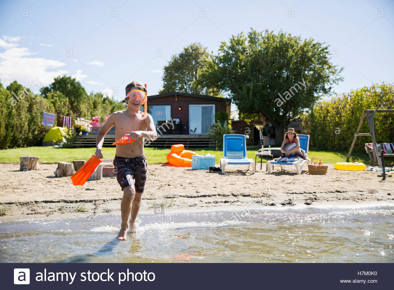 Boy with snorkel and flippers running in sunny summer lake - Stock Image