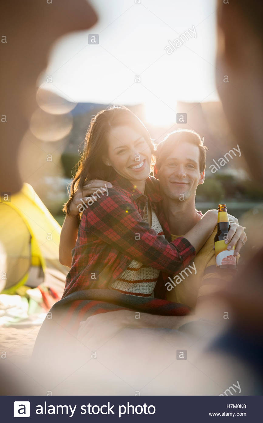 Young couple drinking beer at summer beach campsite - Stock Image
