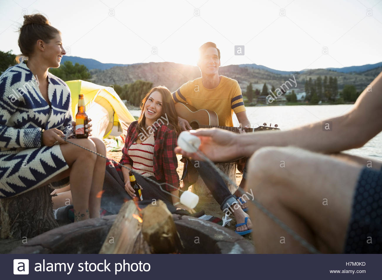 Young friends drinking beer hanging out at campfire on summer lakeside beach - Stock Image