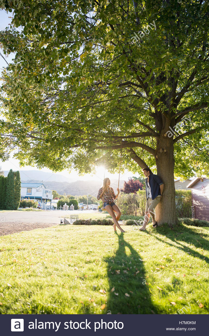 Young couple talking at tree swing in sunny summer yard Stock Photo