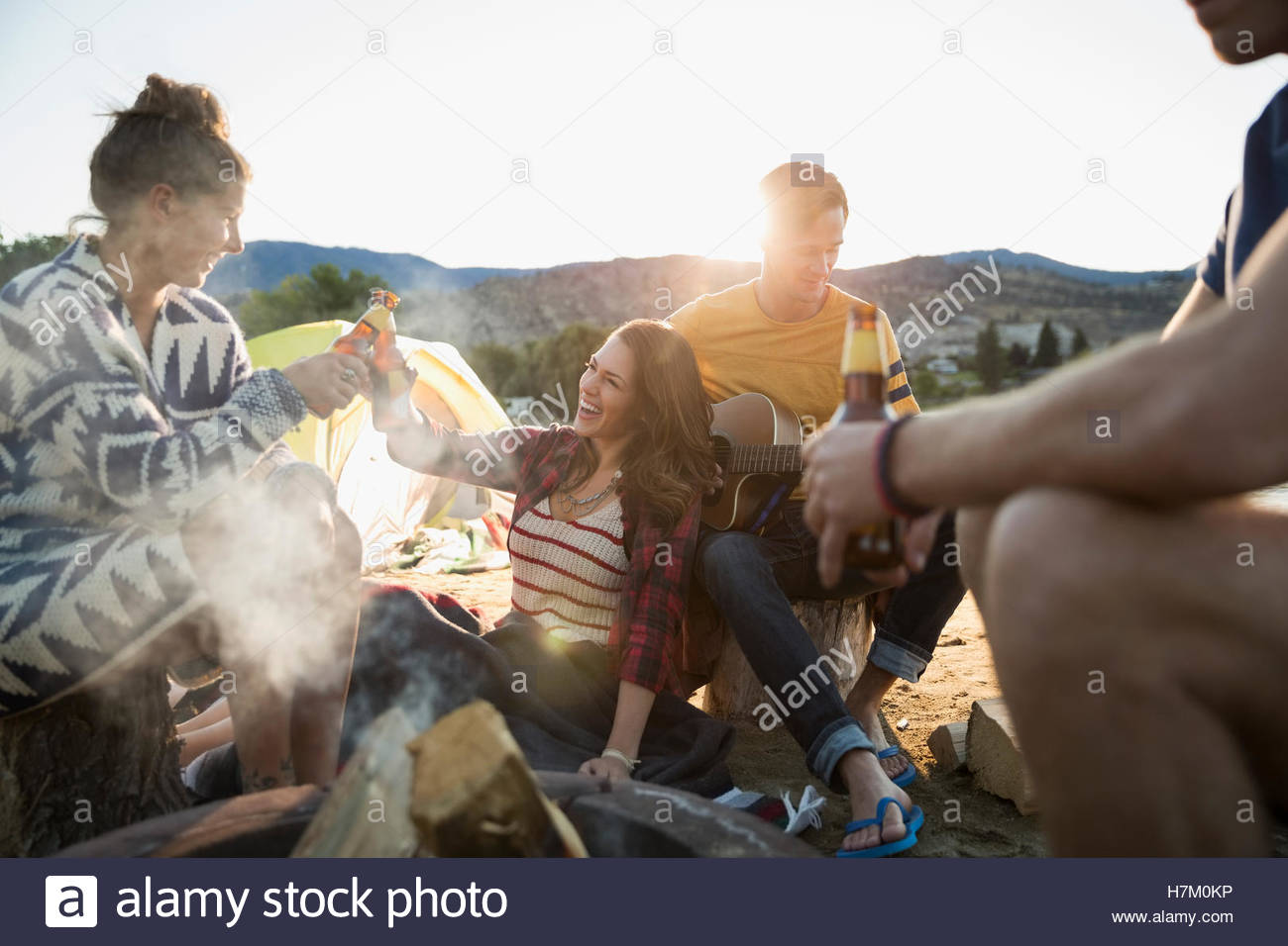 Young friends drinking beer hanging out at campfire on summer beach - Stock Image