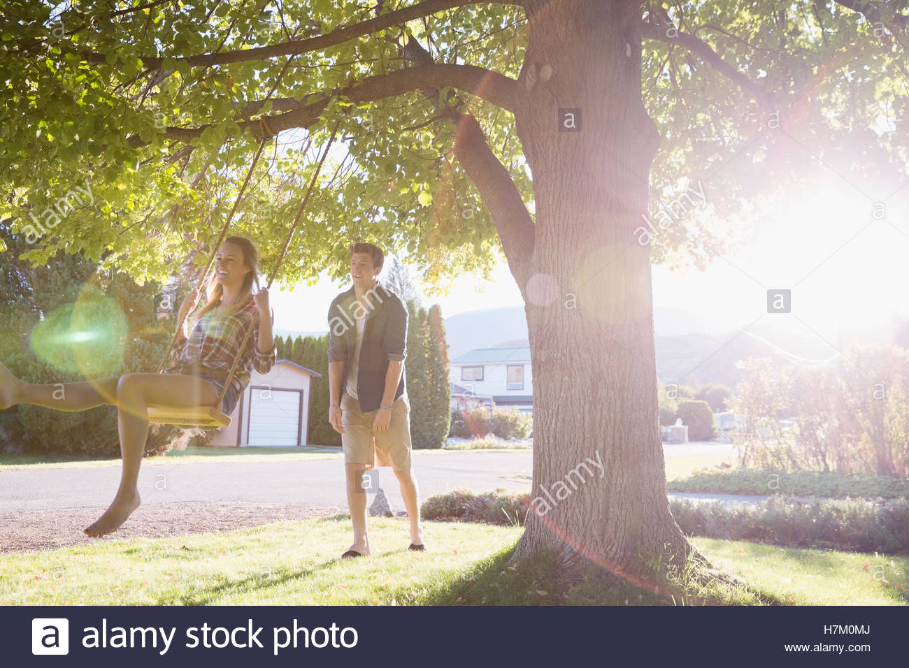 Young couple swinging at tree swing in sunny summer yard - Stock Image