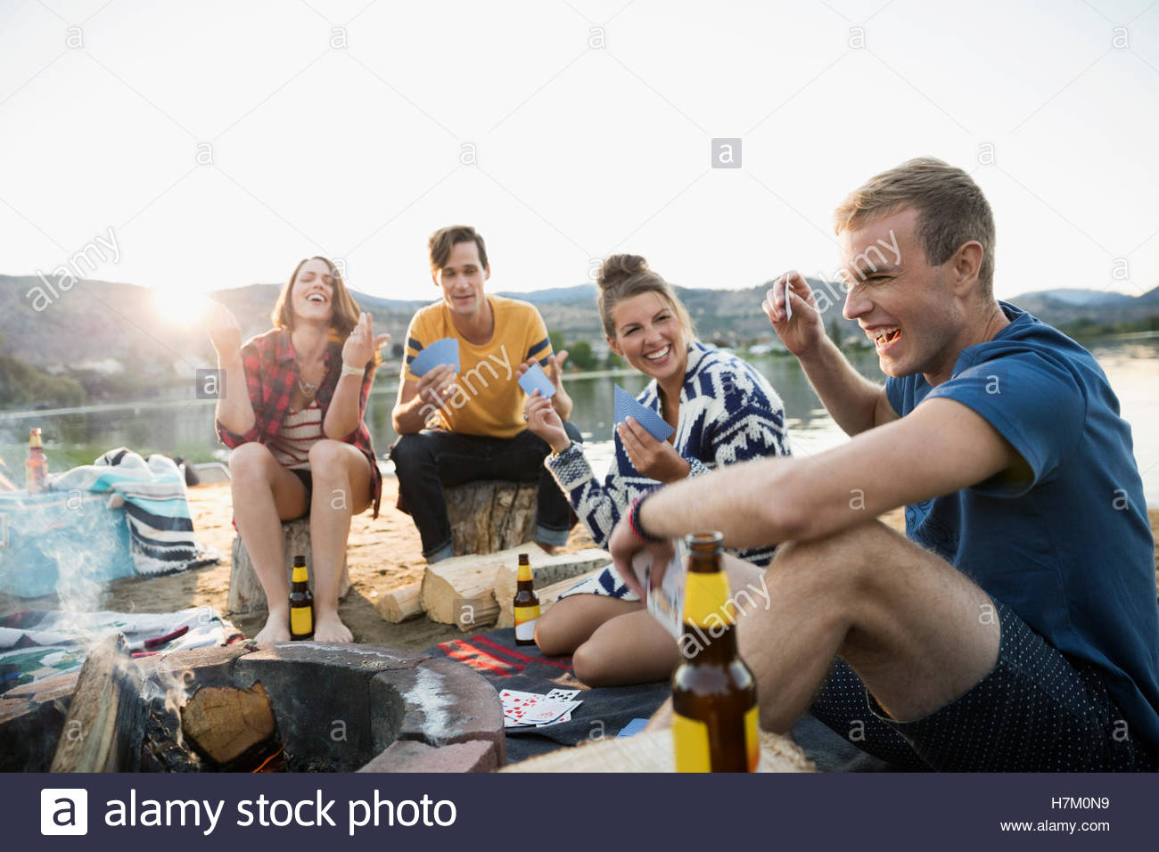 Young couples gesturing playing cards at summer beach campsite - Stock Image