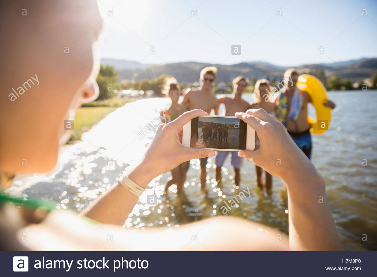 Young woman with camera phone photographing friends at sunny summer lake - Stock Image