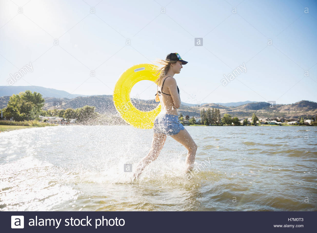 Smiling young woman in bikini running with inner tube in sunny summer lake - Stock Image