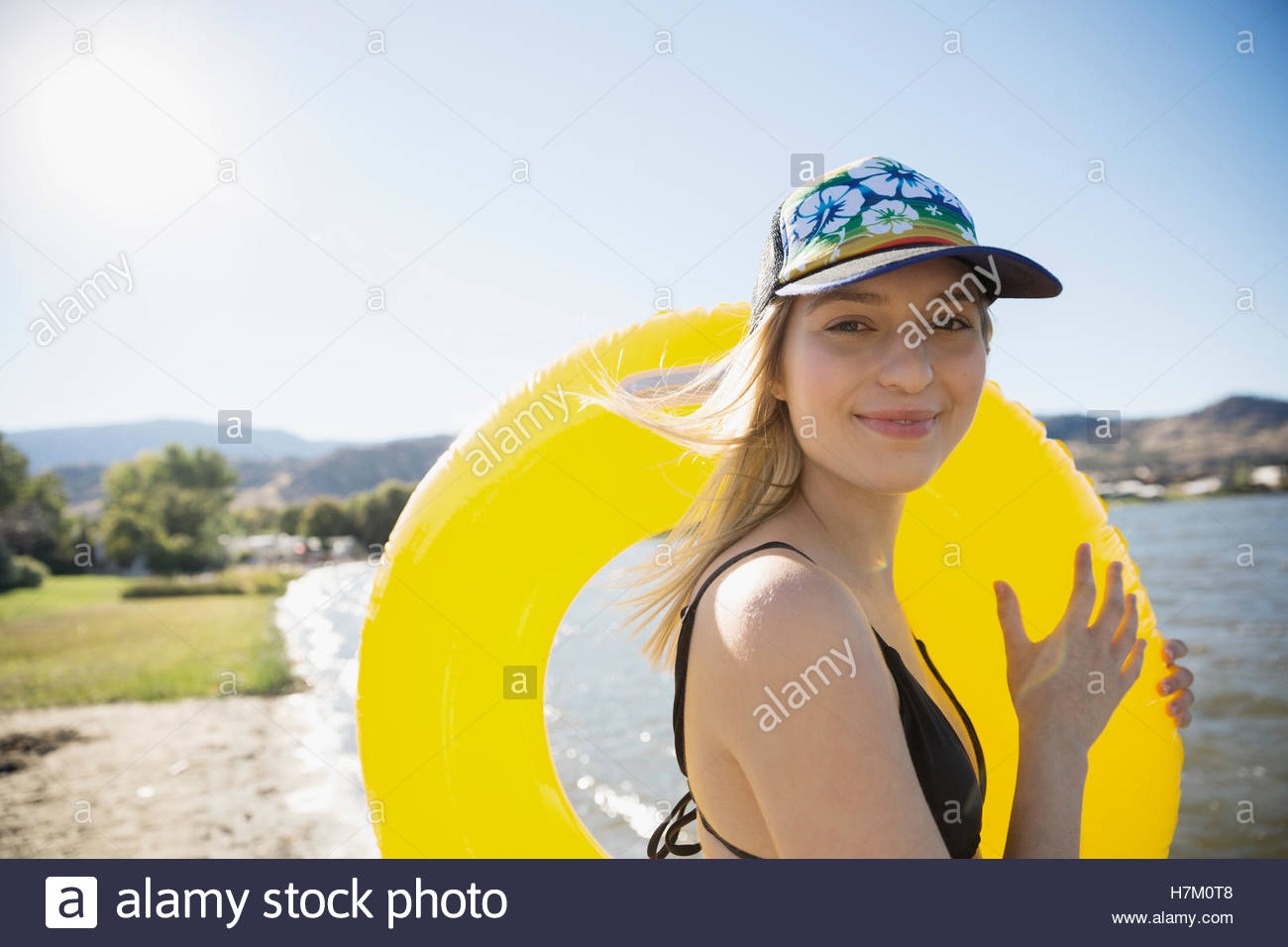 Smiling young woman in bikini with inner tube on sunny summer lake beach - Stock Image