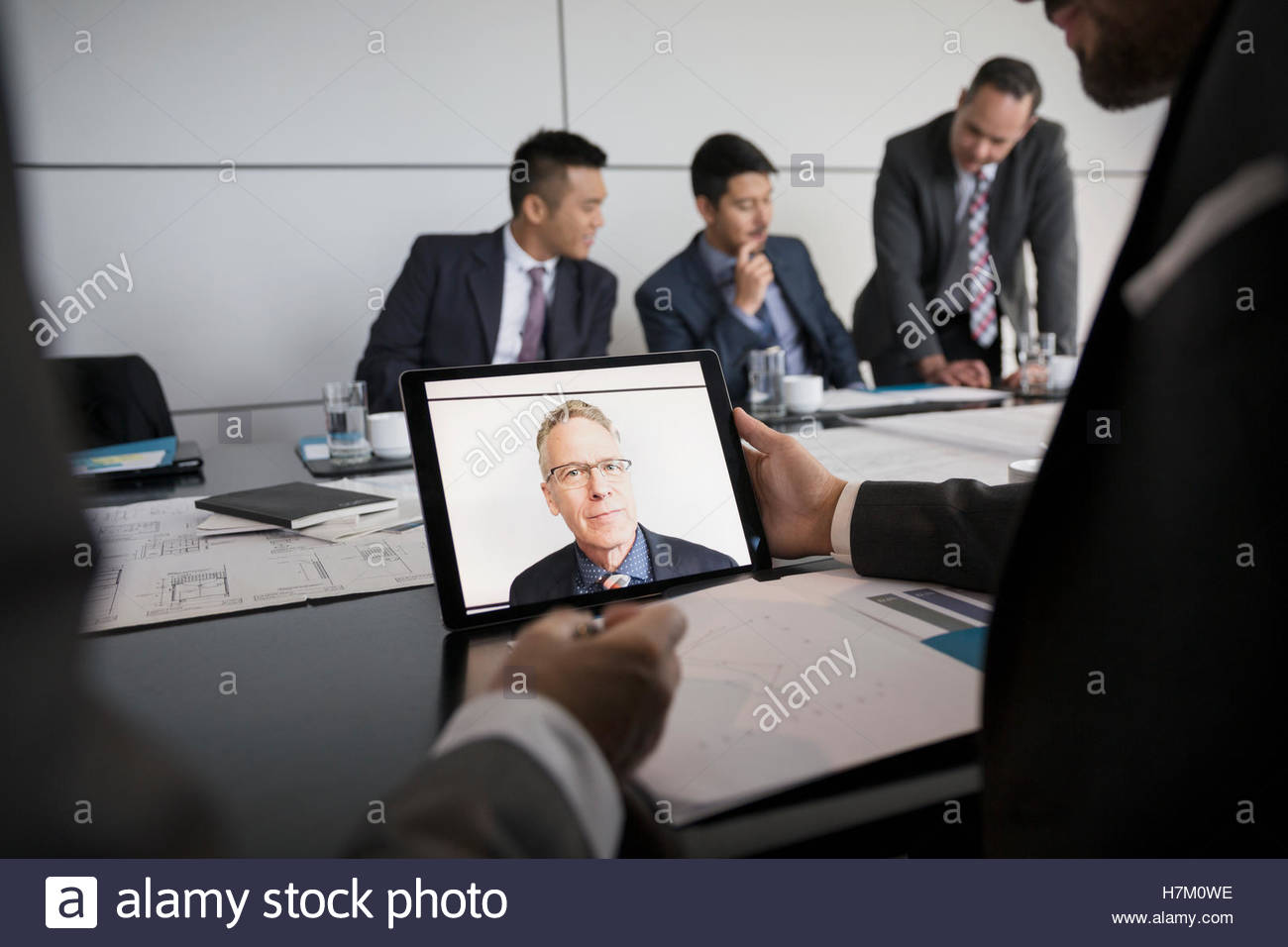 Male architect video conferencing on laptop in conference room - Stock Image