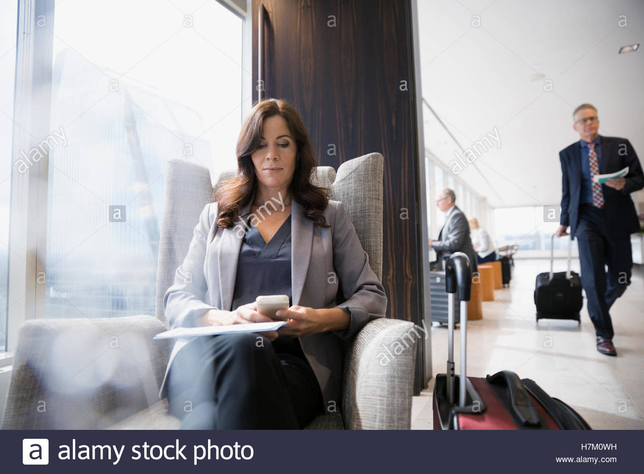 Businesswoman with luggage texting in airport lounge - Stock Image