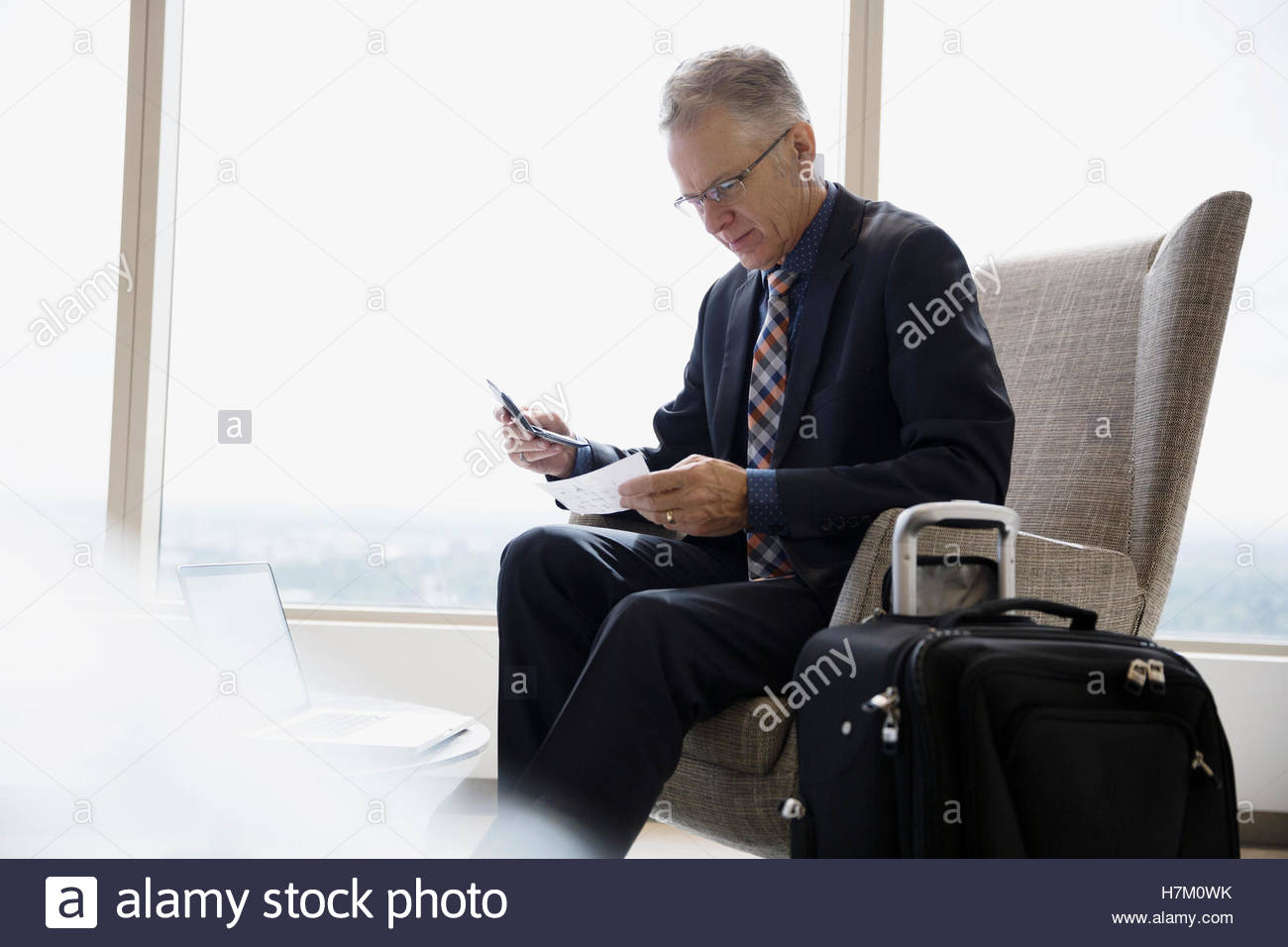 Businessman with luggage checking ticket in airport lounge - Stock Image