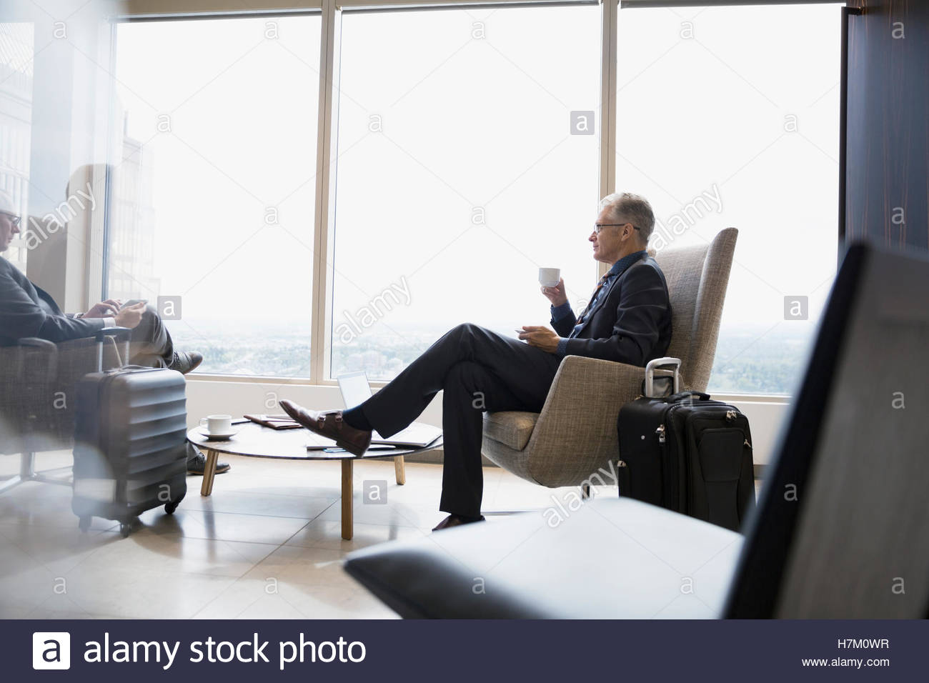 Businessman with luggage drinking coffee in airport lounge - Stock Image