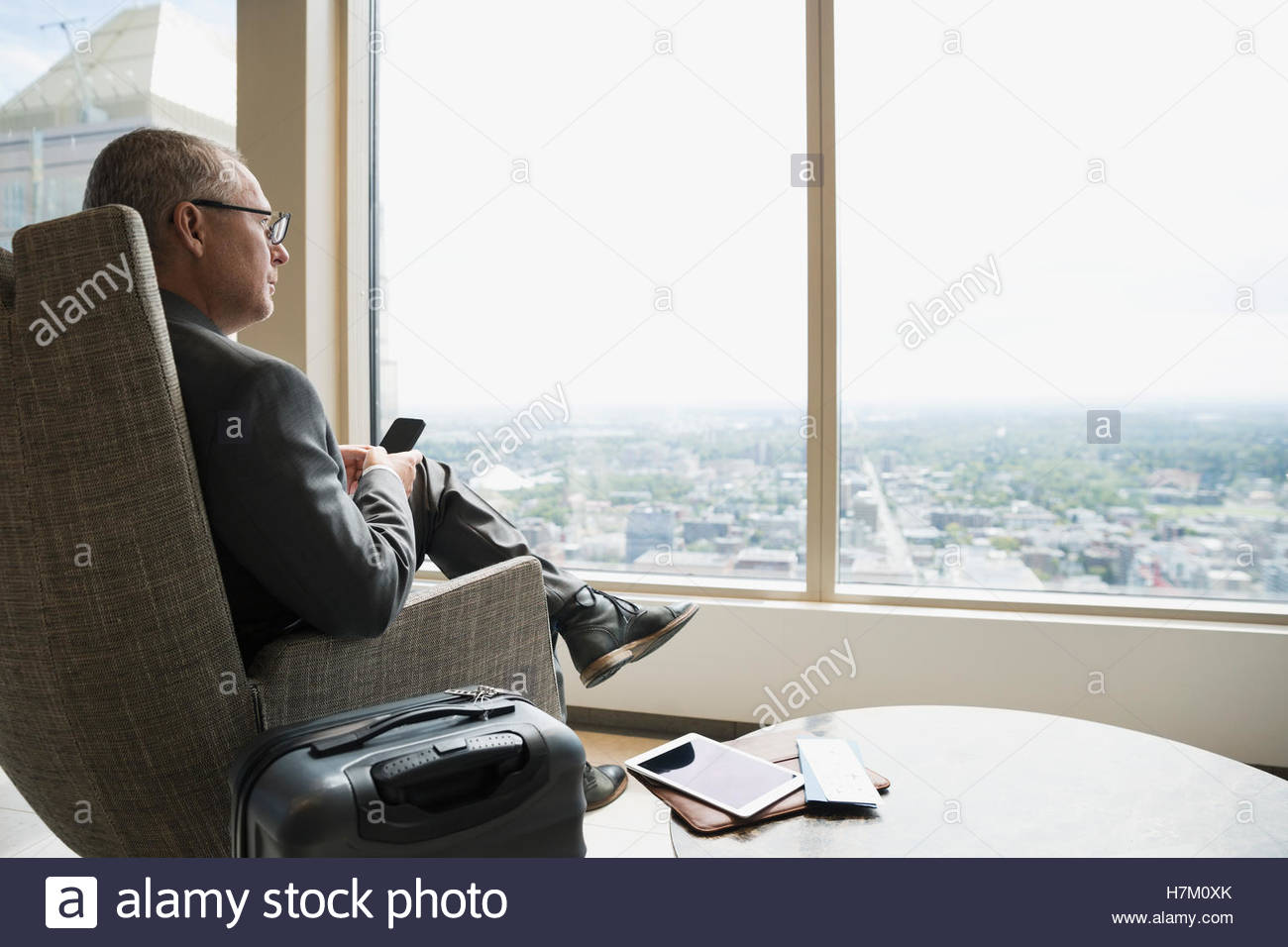 Pensive businessman with luggage texting looking out window in airport lounge - Stock Image